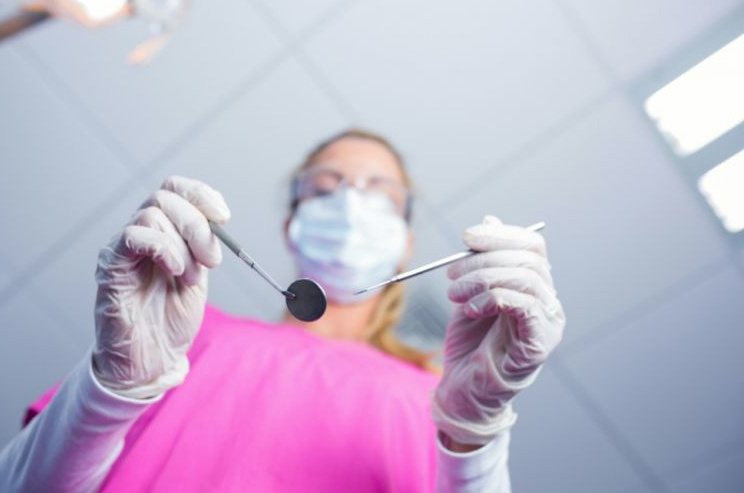dentist-in-surgical-mask-holding-tools-over-PB7FHLY-768x511