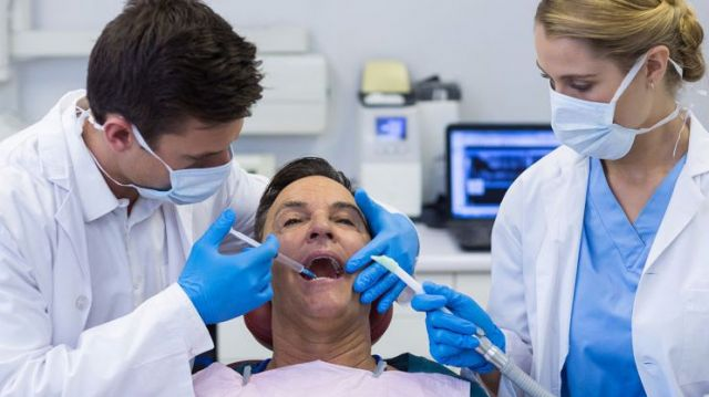Dentist administering anesthesia to patient with nurse looking: Anesthesia Stockton, CA