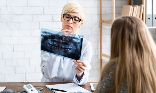 Dentist examining x-rays in the office - California Oral Surgery, CA
