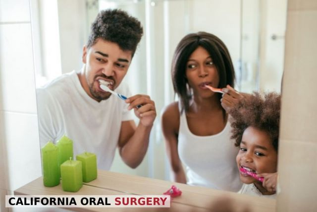A mother and father brushing their teeth with little daughter for healthy kids teeth - Stockton, CA