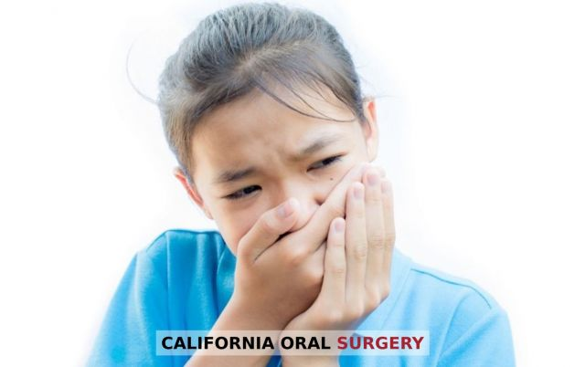 Asian girl holding her mouth in pain because of dry socket - Stockton, CA